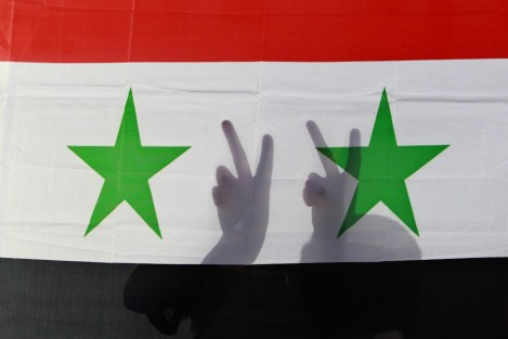 syrian-protester-gestures-victory-signs-behind-their-national-flag